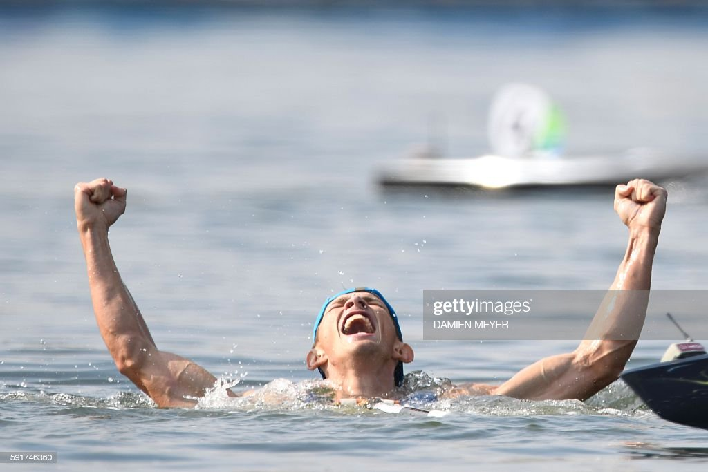 TOPSHOT - Ukraine's Iurii Cheban celebrates by jumping in the water after the Men's Canoe Single (C1) 200m final at the Lagoa Stadium during the Rio 2016 Olympic Games in Rio de Janeiro on August 18, 2016. / AFP / Damien MEYER