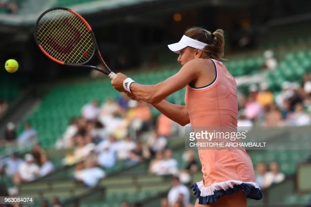 Ukraine's Kateryna Kozlova plays a return to Latvia's Jelena Ostapenko during their women's singles first round match on day one of The Roland Garros...