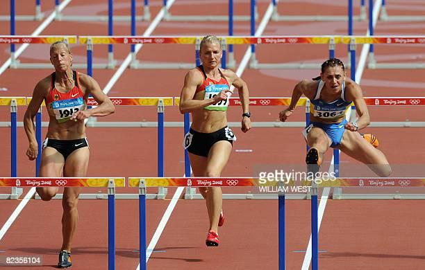 Ukraine's Lyudmila Blonska competes against Germany's Jennifer Oeser and Lilli Schwarzkopf during the women's Heptathlon 100m Hurdles heat 4 at the...