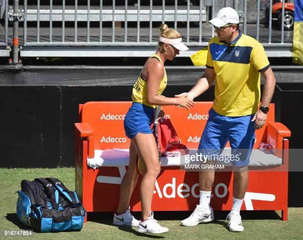 Ukraine's Marta Kostyuk speaks with team captain Mikhail Filima speak during her women's reverse singles Federation Cup tennis match against...