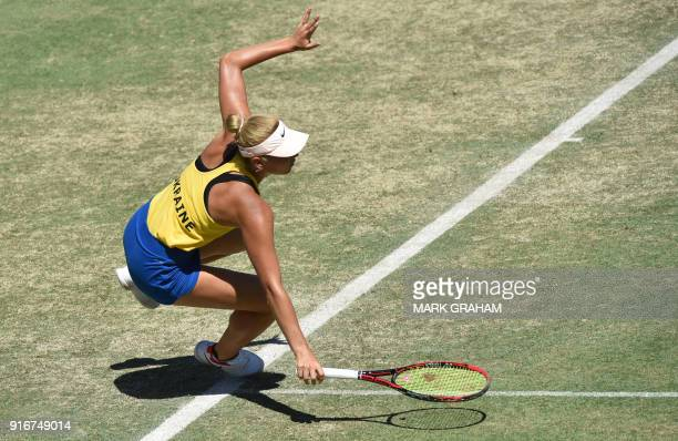 Ukraine's Marta Kostyuk stumbles while playing against Australia's Ashleigh Barty in their women's reverse singles Federation Cup tennis match in...