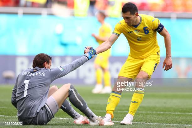 Ukraine's midfielder Taras Stepanenko helps up North Macedonia's goalkeeper Stole Dimitrievski after the UEFA EURO 2020 Group C football match...
