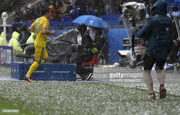 Ukraine's midfielder Yevhen Konoplyanka leaves the pitch during a hailstorm during the Euro 2016 group C football match between Ukraine and Northern...
