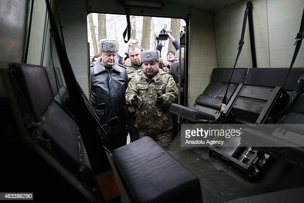 Ukraine's President Petro Poroshenko and Defence Minister Stepan Poltorak inspect military vehicles at the National Guard Training Center in Novy...