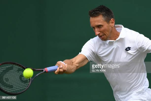Ukraine's Sergiy Stakhovsky returns to US player Sam Querrey during their men's singles second round match on the third day of the 2018 Wimbledon...