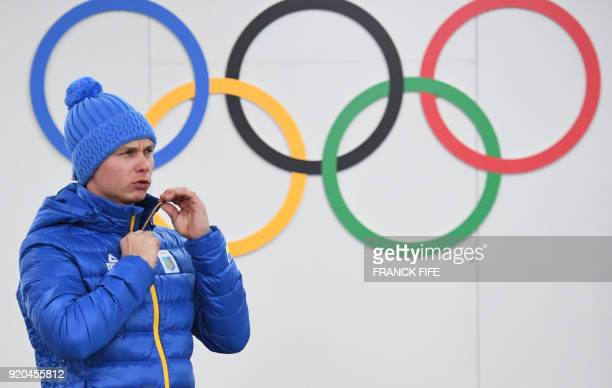 Ukraine's ski aerials gold medallist Oleksandr Abramenko stands in front of Olympic rings backstage at the Athletes' Lounge ahead of the medal...