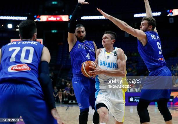 Ukraine's small forward Volodymyr Koniev is marked by Italy's shooting guard Pietro Aradori and power forward Nicolo Melli during their FIBA...