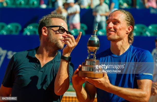 Ukraine's tennis player Alexandr Dolgopolov poses with the trophy beside the director of the Argentina Open tournament Martin Jaite after winning the...