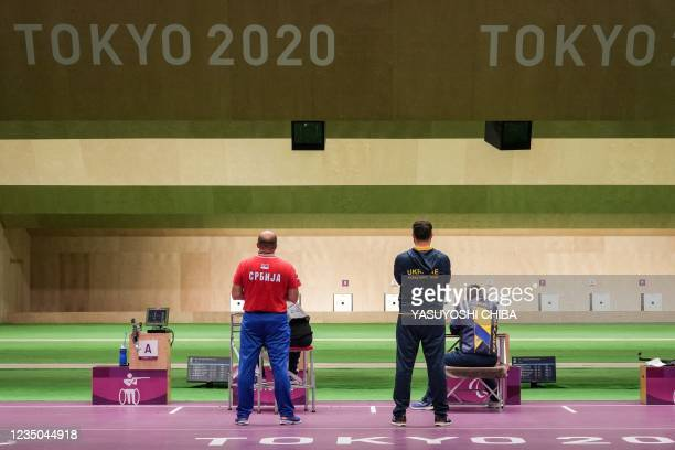 Ukraine's Vasyl Kovalchuk and Serbia's Zdravko Savanovic compete as their assistants look on during the final of the shooting R9 mixed 50m rifle...