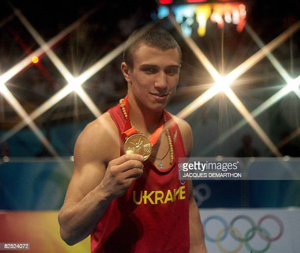 Ukraine's Vasyl Lomachenko celebrates his Featherweight gold medal on August 23 2008 at the Beijing 2008 Olympic Games boxing podium AFP PHOTO /...