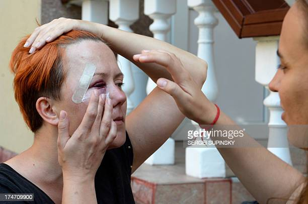 Ukrainian activist and founder of FEMEN Anna Hutsol puts cream on her face as she waits in front a district court in Kiev on July 28 2013 after being...