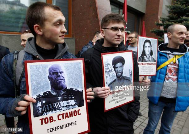 Ukrainian activists of Democratic Ax civil movement hold placards depicting of World of Warcraft game and Marvel characters, as they protest against...