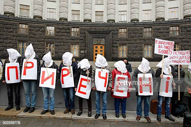 Ukrainian activists who are suffering from HIV AIDS and hepatitis stand with bags on their heads and the noose around his neck as a symbol that the...
