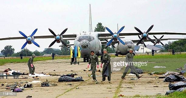 Ukrainian air force officers carry a body of a victim killed when Su27 fighter plane crashed into a huge crowd of spectators at an air show in the...