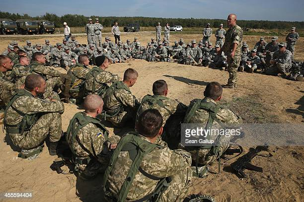 Ukrainian and US soldiers listen to a Ukrainian major speak on traffic control post techniques on the third day of the 'Rapid Trident' bilateral...