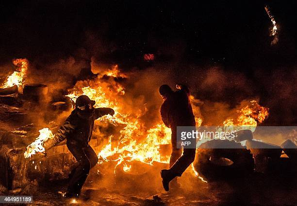 Ukrainian antigovernment protesters throw Molotov cocktails during clashes with riot police in central Kiev early on January 25 2014 Protesters and...