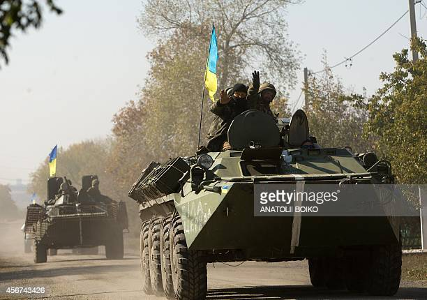 Ukrainian armored personnel carriers patrol along a road leading to the town of Debaltseve in the Donetsk region on October 6 2014 The first European...
