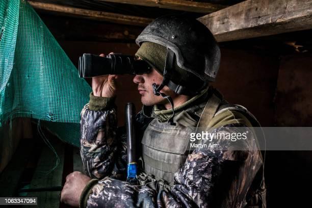 Ukrainian Army soldier looks through binoculars at a frontline position in Pisky one of the most dangerous in the hostilities between Ukrainian...