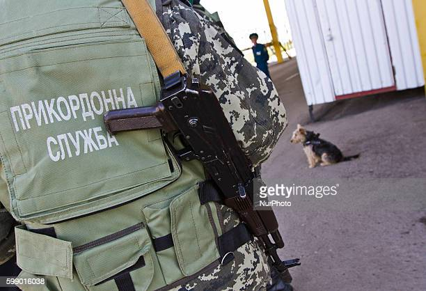 Ukrainian border guard with a gun stays at the BCP Customs Control Zone on the border between Ukraine and Moldova