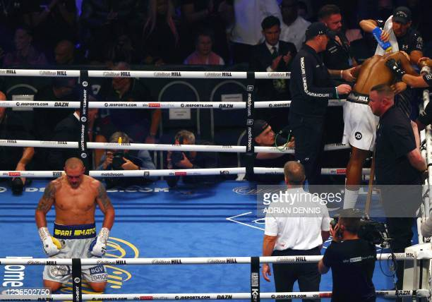 Ukrainian boxer Oleksandr Usyk kneels on the canvas as British heavyweight champion boxer Anthony Joshua goes to his corner at the end of their...