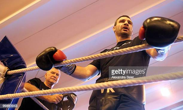 Ukrainian boxer Vitali Klitschko talks to spectators as his coach Fritz Sdunek listens to him during a training session on May 18 2010 in Going...