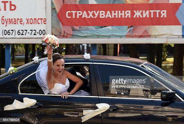Ukrainian bride celebrates her wedding while in her car in a street of the key southeastern port city of Mariupol, on September 6, 2014 after a...