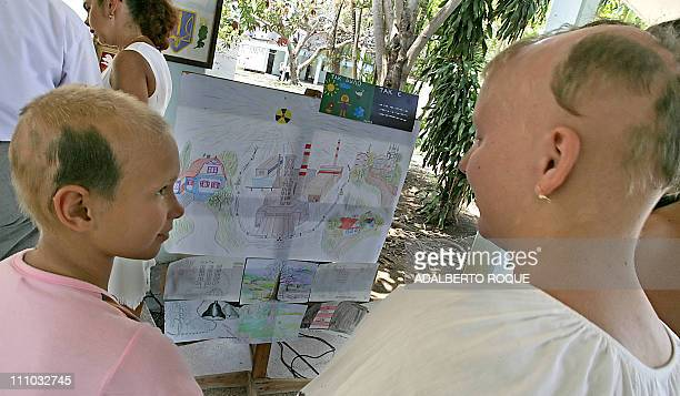 Ukrainian children Darina Ianoskaya and Ania Skurajod late victims of the 1986 Chernobyl nuclear plant accident look 26 April 2006 at drawings made...