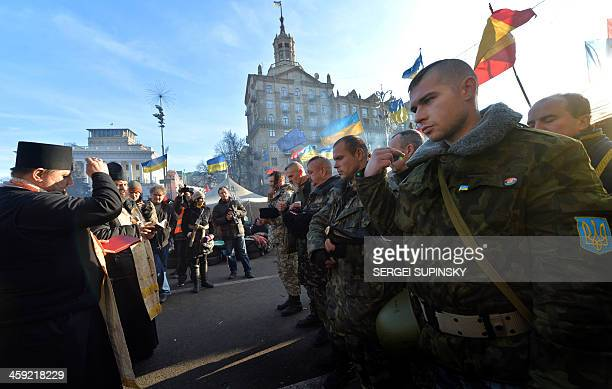 Ukrainian cossaks cross themself during a service before taking their guarding duty at the camp of the proEU opposition at Kiev's Independence Square...