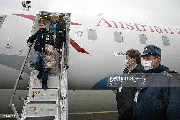 Ukrainian customs officers wear protective masks as passengers disembark from an Austrian airlines plane in the eastern Ukrainian city of Donetsk on...
