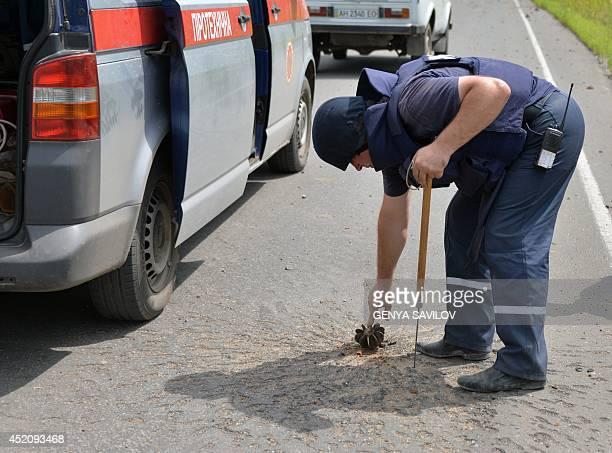 A Ukrainian deminer neutralizes on July 13 2014 mines and other explosives in the village of Semenovka near the eastern Ukrainian city of Slavyansk...