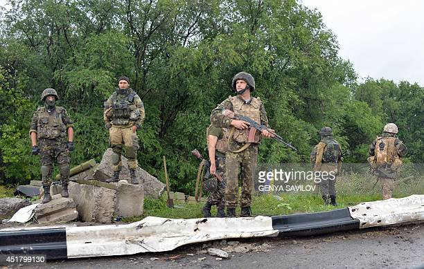 Ukrainian forces servicemen guard near a destroyed tank of pro-Russian militants on the check-point at Slavyansk on the road to Kramatorsk on July 7,...