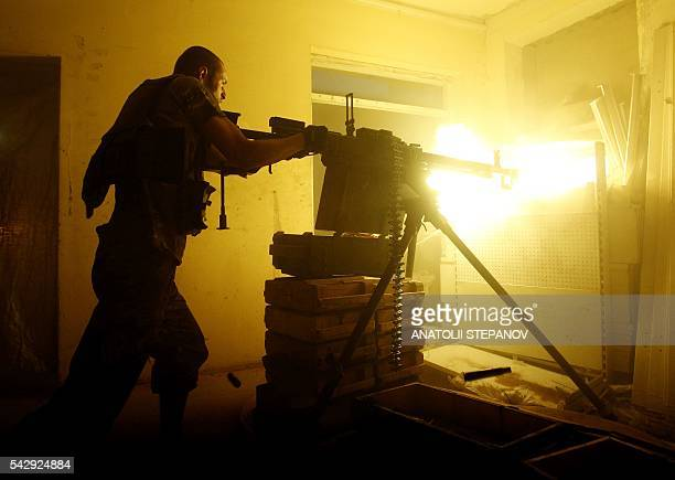 Ukrainian Forces soldier fires a heavy machine gun during a battle with proRussian separatists at Avdeyevka in Ukraine's Donetsk region on June 25...
