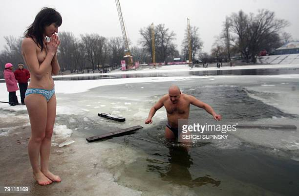 A Ukrainian girl prays before bathing in icy water of the Dnieper river during celebration of the Epiphany holiday 19 January 2008 Epiphany is one...