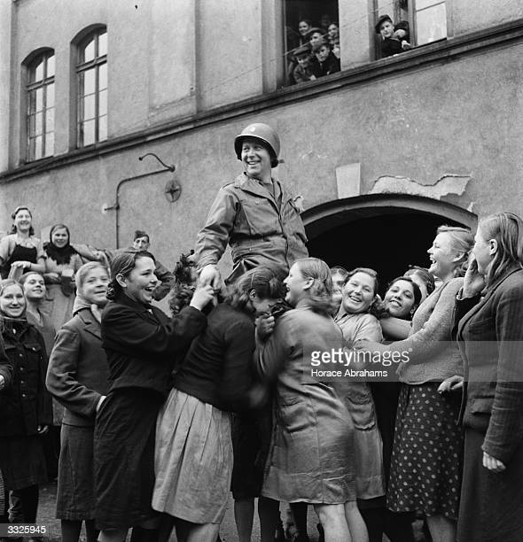 Ukrainian girls who were made to work in a German ammunition factory hoist an American soldier onto their shoulders after troops liberated them from...