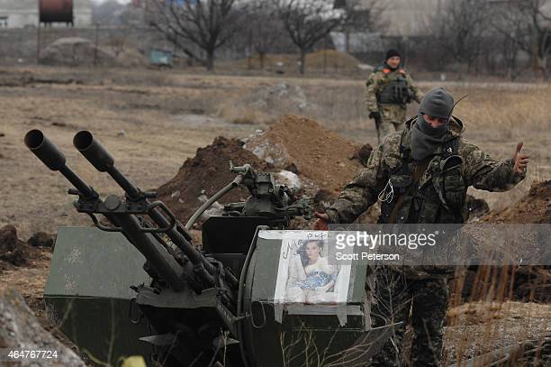 A Ukrainian government soldier laughs at a portrait of a partially nude woman on his 127mm Dushka antiaircraft gun as Ukrainian troops dig in to...