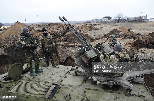 Ukrainian government soldiers dig trenches and deploy 127mm Dushka antiaircraft guns to defend against a possible advance by Russianbacked rebel...