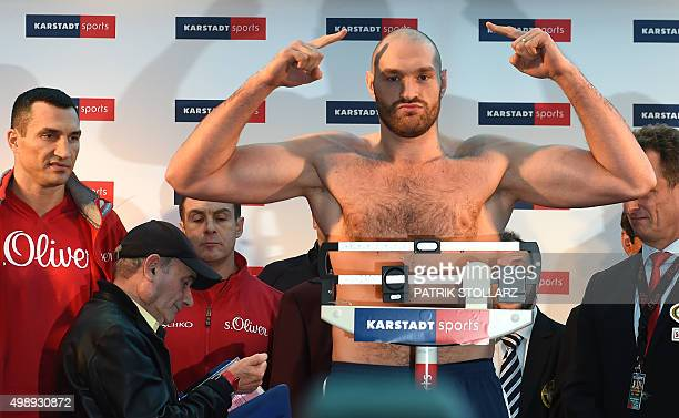 Ukrainian Heavyweight World Champion Wladimir Klitschko looks on as his British challenger Tyson Fury stands on the scales during their official...