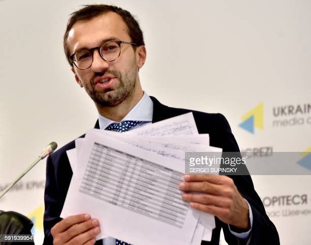 Ukrainian journalist and member of parliament Serhiy Leshchenko holds pages showing allegedly signings of payments to Donald Trump's presidential...