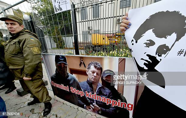 Ukrainian journalists hold placards depicting their colleague Roman Sushchenko during a protest to call for the release of a Ukrainian journalist...