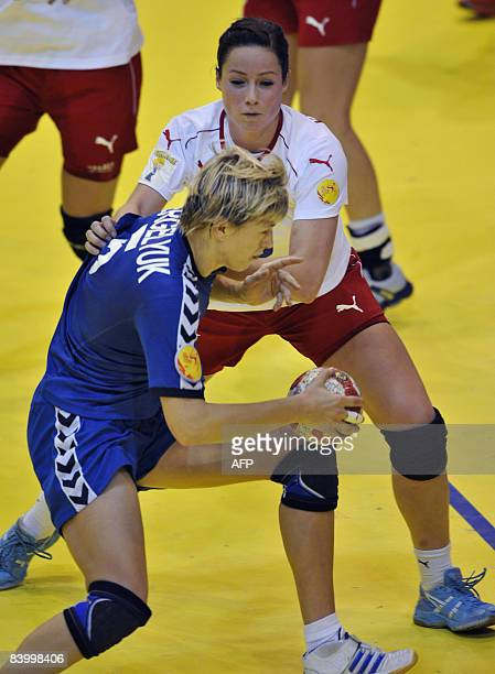 Ukrainian Maryna Vergeliuk is pushed by Danish Kamilla Kristensen during the 8th Women's Handball European Championships match on December 11 2008 in...