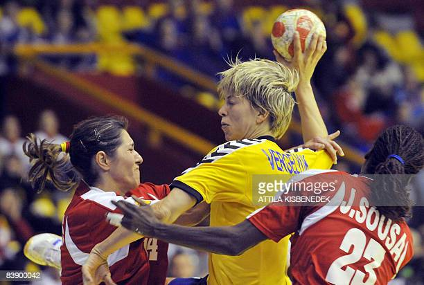 Ukrainian Maryna Vergeliuk scores a goal between Portuguese Renate Tavares and Juliana Sousa during the 8th Women's Handball European Championships...