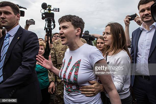 Ukrainian military pilot Nadiya Savchenko is held back by her sister Vira Savchenko while surrounded by media upon her arrival at Kyiv Boryspil...