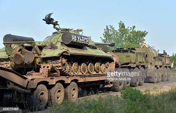 Ukrainian military vehicles pass on August 1 2014 near the village of Debaltseve in the Donetsk region eastern Ukraine while carrying a WWII IS3...