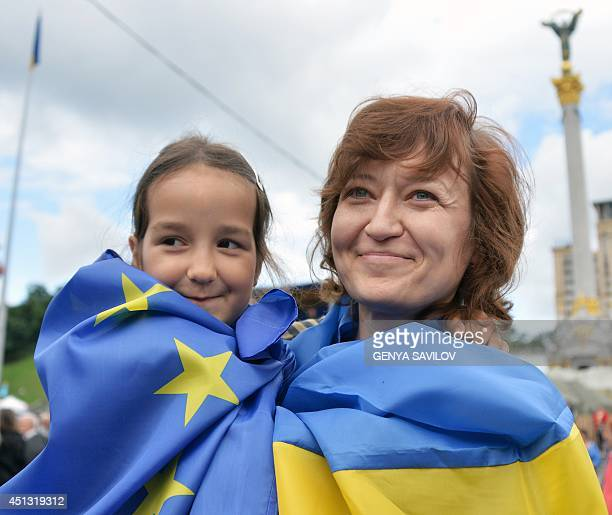 A Ukrainian mother wearing a national flag holds her daughter wearing a European Union flag as they attend a gathering in the iconic Maidan square in...