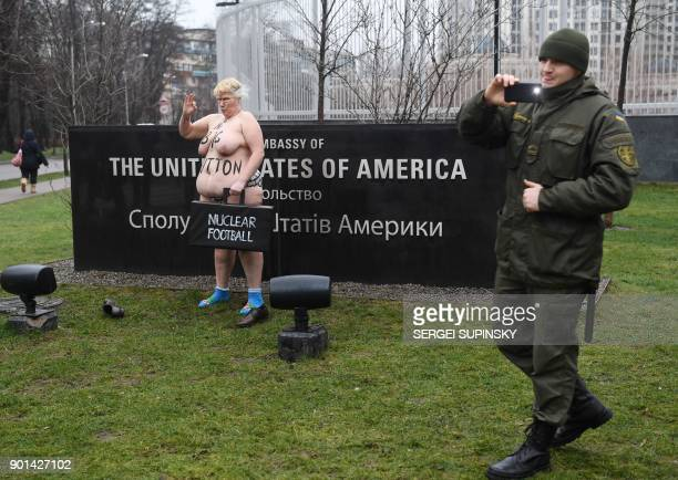 A Ukrainian national guard serviceman guarding the US embassy in Kiev takes pictures as a topless activist of the Ukrainian women's movement Femen...