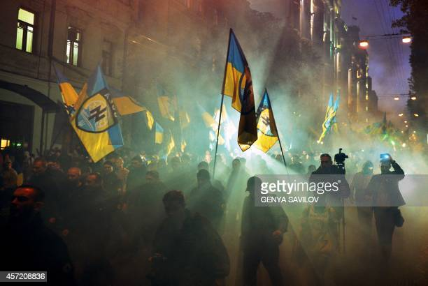 Ukrainian nationalists and servicemen of the Azov battalion demonstrate in Kiev on October 14, 2014 to mark the founding of the Ukrainian Insurgent...