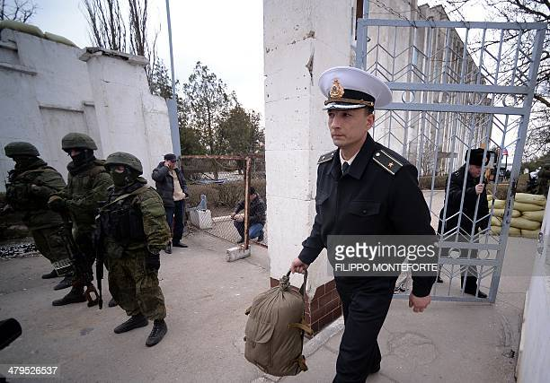 A Ukrainian officer leaves as Russian soldiers stand guard after they took control of the Ukrainian navy south headquarters base in Novoozerne on...