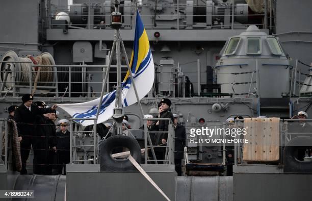 Ukrainian officers raise a navy flag as they stand guard on board the Ukrainian navy ship Slavutych in the port of Sevastopol, where a Ukrainian navy...