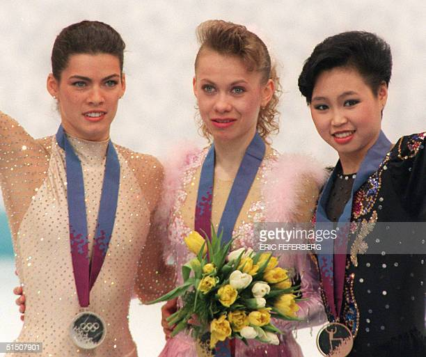 Ukrainian Oksana Baiul Nancy Kerrigan from the United States and Chinese Chen Lu smile on the podium during the medals' ceremony of the women's...