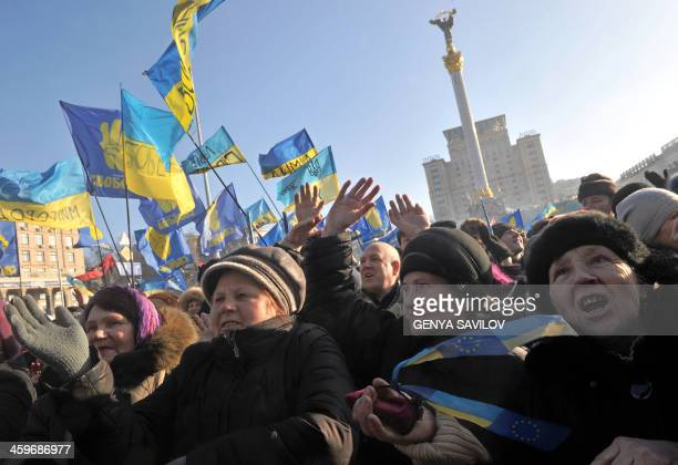 Ukrainian opposition supporters raise their hands and shout slogans during a mass rally on Independence Square in Kiev on December 29 2013 Tens of...